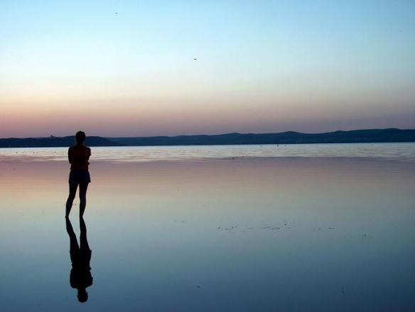 woman standing water at sunset