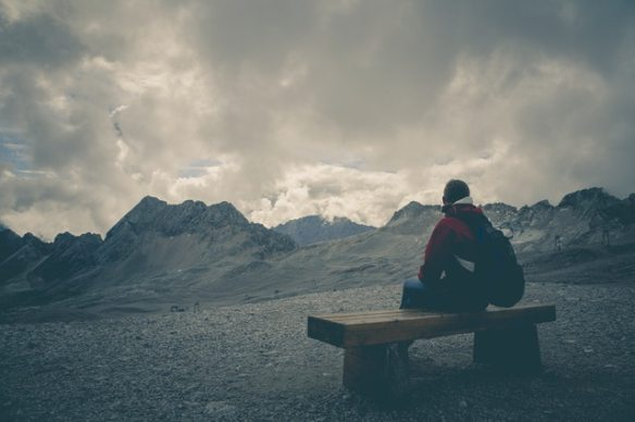 man sitting on bench with distant mountains