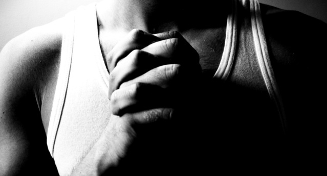 male clasping hands in prayer