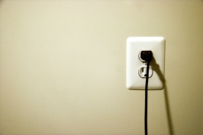 U.S. wall outlet with cord plugged in