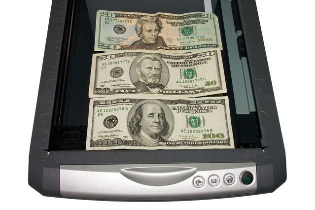 three bills of United States currency on scanner