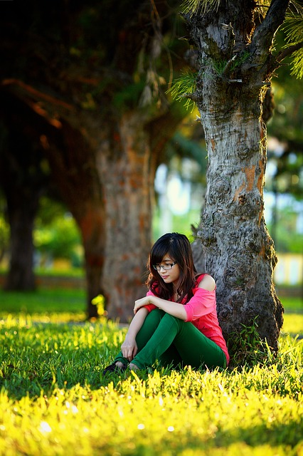 young woman sitting by tree