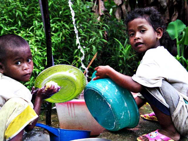 two indigenous children washing dishes
