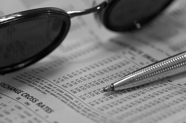 glasses and pen on sheet of financial rates