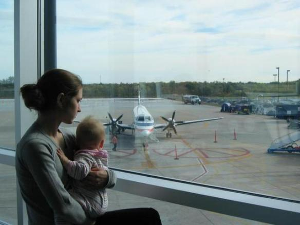 mother baby looking at plane