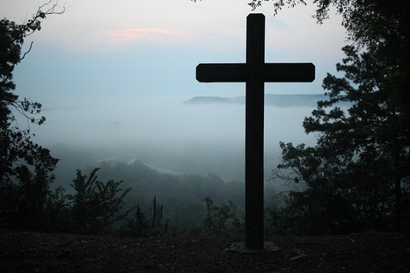 A silhouette of a cross and brush with fog, sky and mountains in the distance.