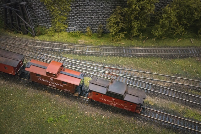 An overhead view of three red cabooses sitting on one of several train tracks including one that curves away from the others.