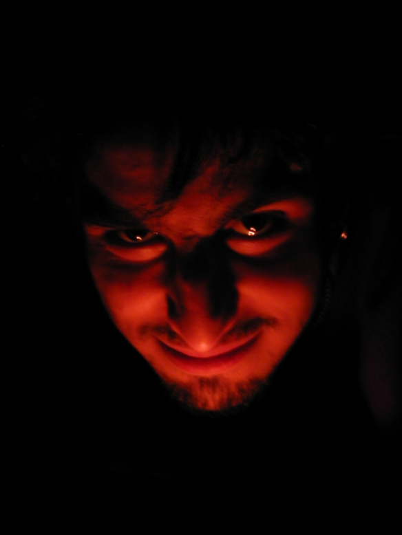 man with devilish appearance with red candlelight underneath face