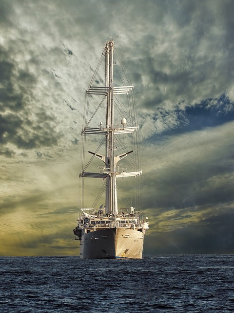 Large white modern sailing ship with sails rolled up