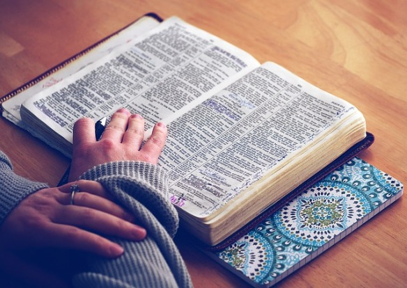 Open Bible laying flat on hardwood table with hands folded and resting partially near lower portion of book