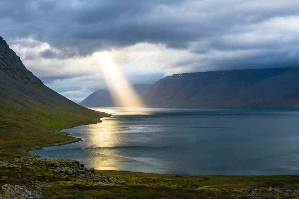 A beam of sunlight shining through grey clouds on a body of water between two low mountain ranges