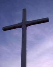 a picture of a wooden cross with a partly cloudy sky behind at sunset