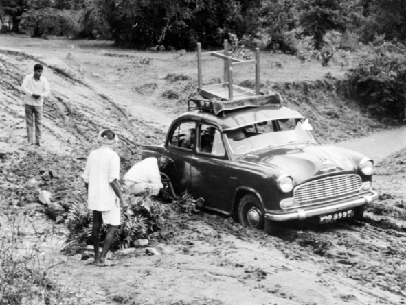 Black and white photo of an old car stuck in the mud