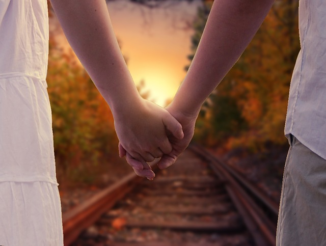 young couple holding hands while walking down a railroad track