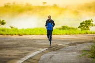 a man jogging on a curved section of road with a yellow foggy background