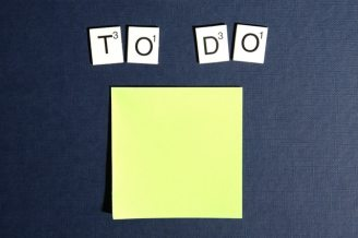 a yellow sticky note with the letters from a Scrabble game above spelling the words 'to' & 'do'