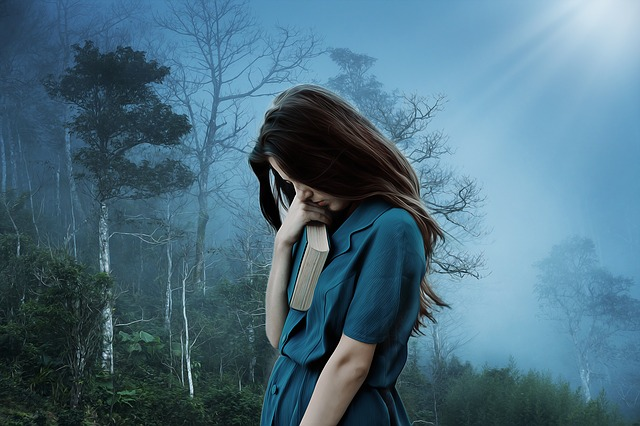 Woman looking downward with book in hand near face with bluish fog and trees in background