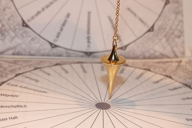 A photo of a gold pendulum swinging on a printed diagram