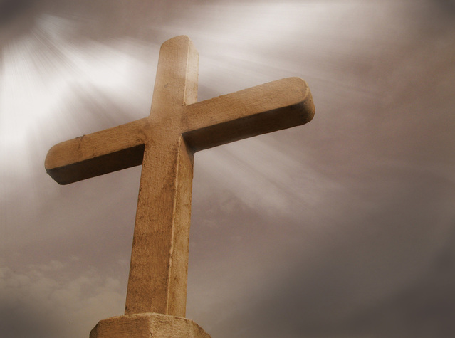 brown concrete cross with light beams shining through thick grey clouds