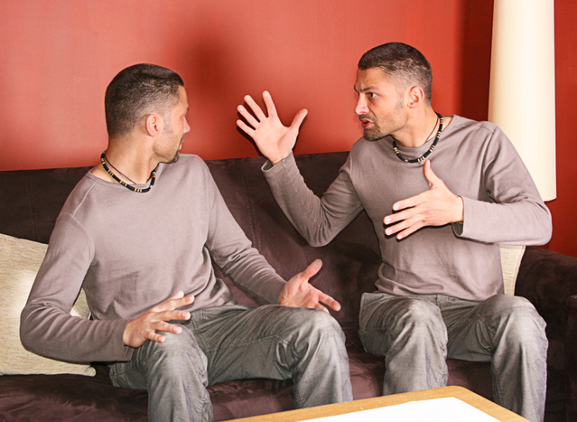 Photo of two identical men seated on couch in argument with one man's hands in the air