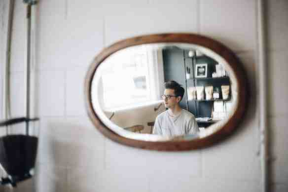 image of seated man with glasses in mirror hanging on tiled wall