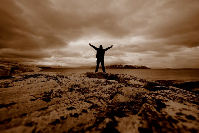 sepia photo of man with arms raised standing on rocky ground facing towards large body of water on cloudy day