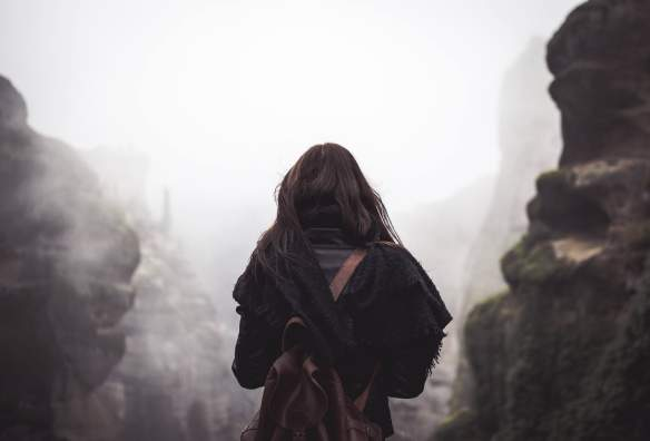 backside of woman hiking on heavy fog path