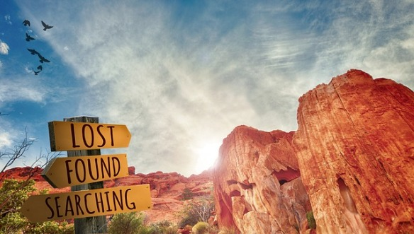 lost, found, searching sign post in rocky desert area