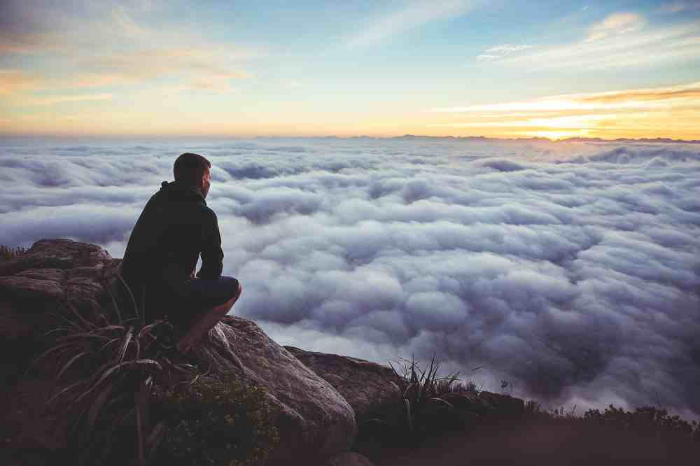 man sitting on mountainside overlooking clouds below