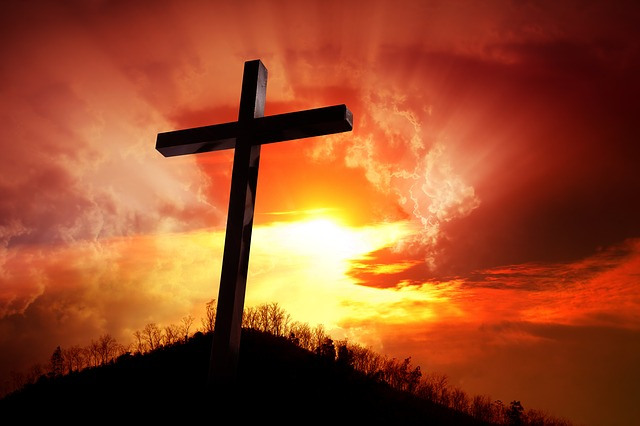 photo of a cross on a hill with sun, clouds and red sky in background