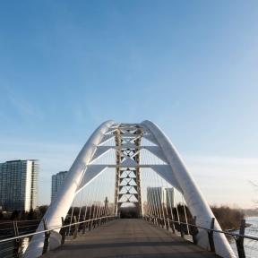 A modern steel arch suspension pedestrian bridge