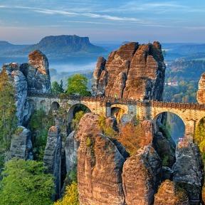A photo of Bastei bridge, a stone arch crossing through a steep mountainous region.