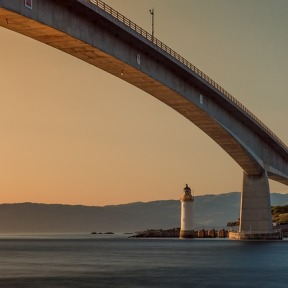 A tall modern bridge over water with lighthouse at end and mountains in background