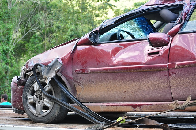 A photo of the side view of a small red car that was involved in an accident.