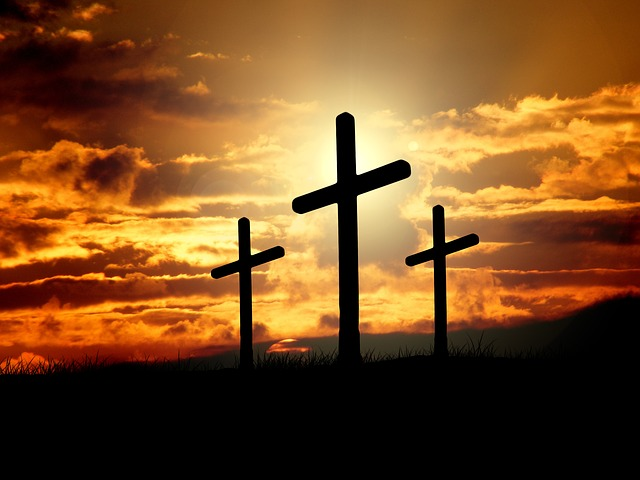A photo of three crosses with sun and clouds in the background.