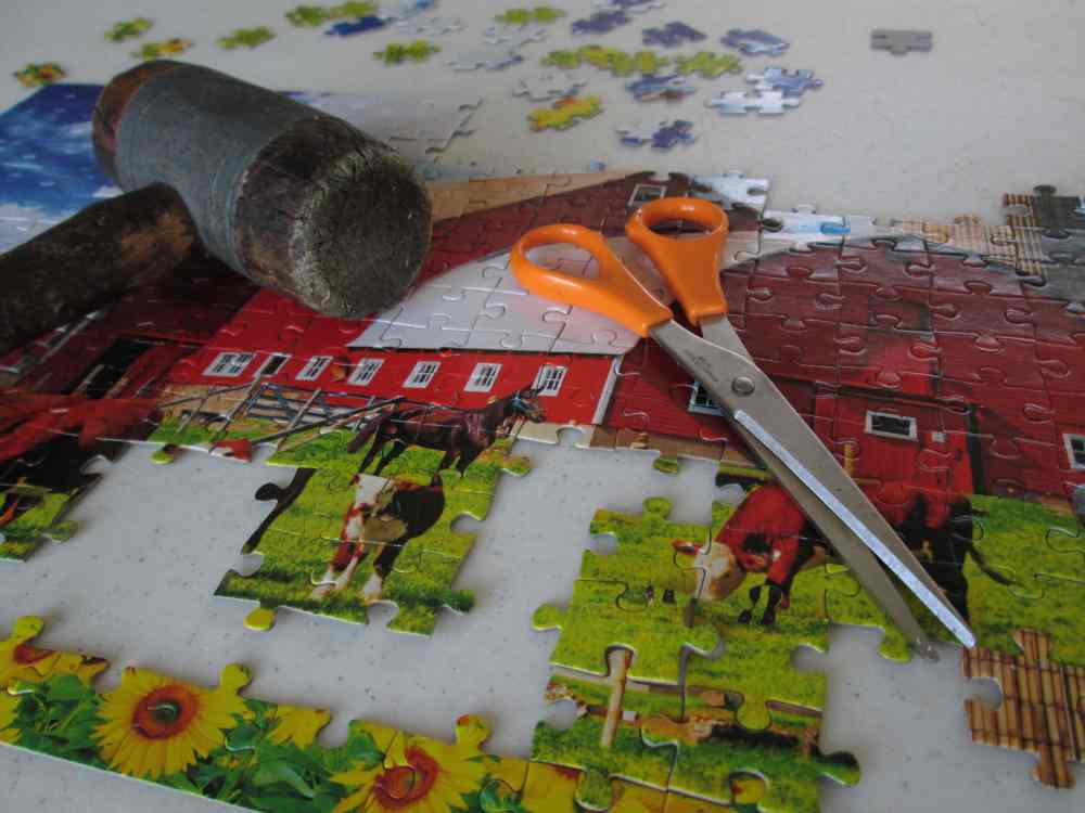 A photo of a puzzle containing several incorrectly placed pieces with a mallet and scissors resting on top