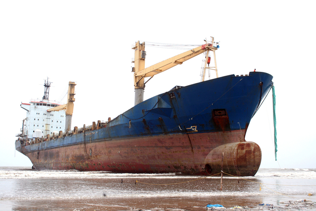 large empty container ship run aground on sand