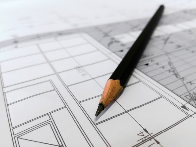A photo of a pencil laying on an architectural drawing that is fading as a blur into the background