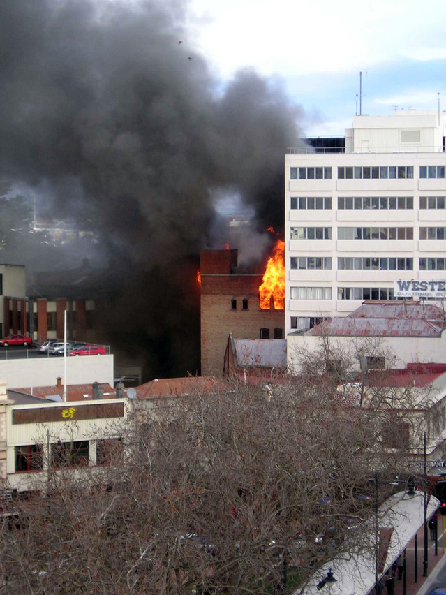 photo of flames and smoke coming from a small building in a city