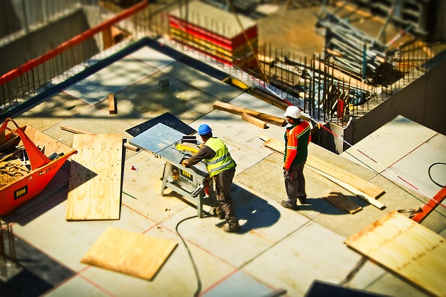 An overhead view of two men at a construction site with one cutting wood on a table saw