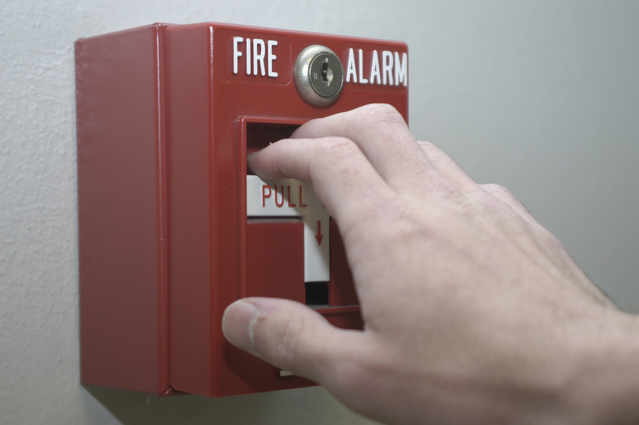 Photo of hand over fire alarm pull box