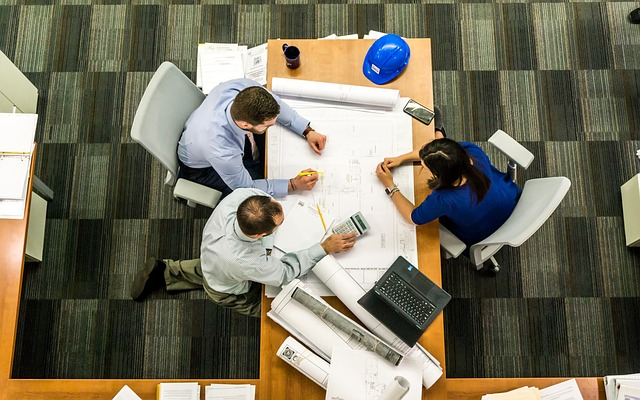 overhead photo of three people in meeting at table containg blueprint