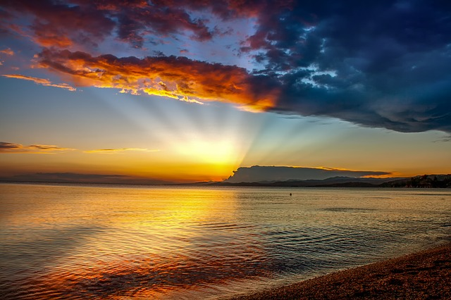 photo of sunset behind clouds over water with sunbeams highlighting clouds above and water below