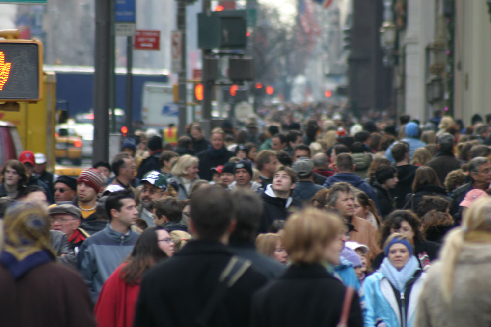 A crowd of people walking on a street in New York City