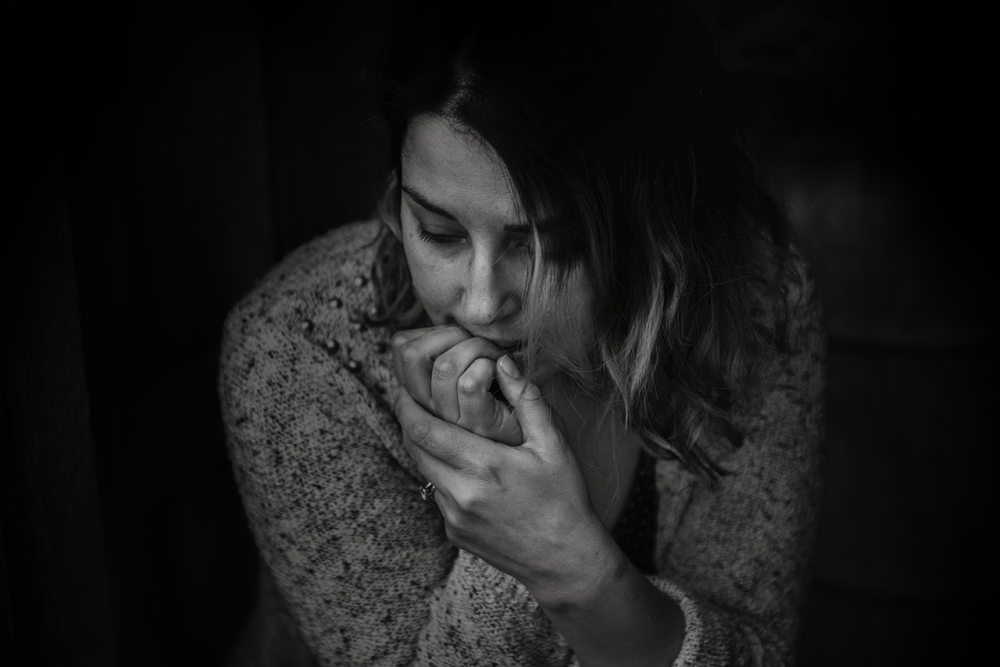 black and white picture of a woman leaning over with fingers of right hand in mouth with a worried or depressed expression