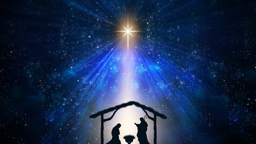 A graphical image of a manger scene with a star above in a blue-black starry night scene.