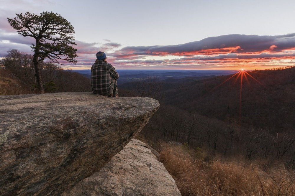 A person in a plaid shirt sitting on a cliff overlooking a dark valley with the sun rising in the background