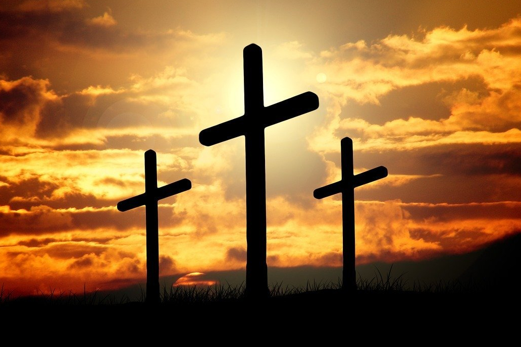 Silhouette of three crosses on hillside with orange sky containing clouds and sun in the background