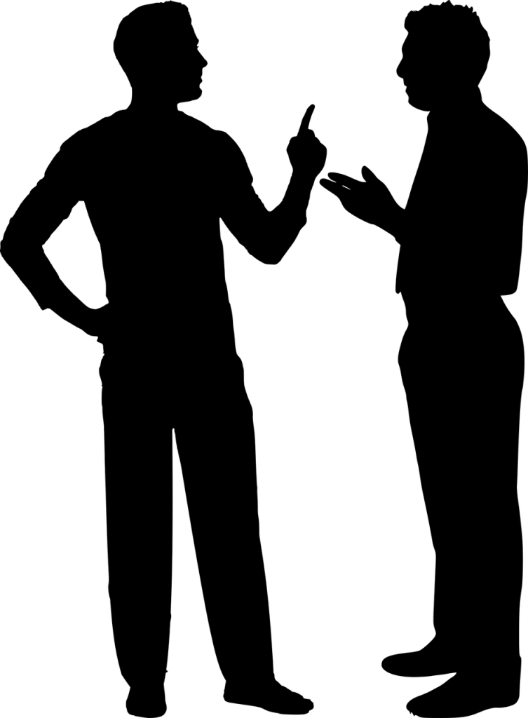 Silhouette of two men standing in an argument