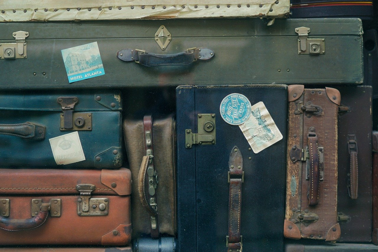 A collection of assorted old baggage displayed with handles outward